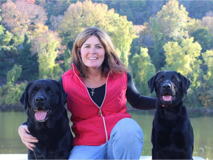 Smiling Loretta Cleveland, owner and trainer of The Positive Pooch, with two black labs by her sides