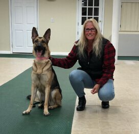 Our dog walker, Dina Brooks, is posing for a picture with a german shepherd